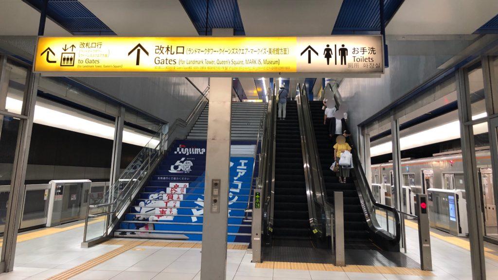 みなとみらい線の駅のホームから階段とエスカレーターを写したもの。上部に「クイーンズスクエア方面」と表示がでている。