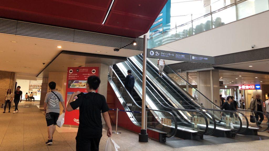 ショッピングモール(クイーンズスクエア)の店内の写真。画面左側は奥に進む通路。右側は更に上の階に行くためのエスカレーター。