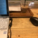 STORY CAFEのテーブルの上。パソコンとトレイ、PC用マウスが写っている。トレイには飲みかけののみもの。